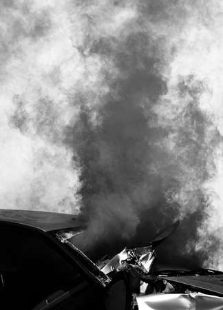 dense smoke from a damaged car after the road accident