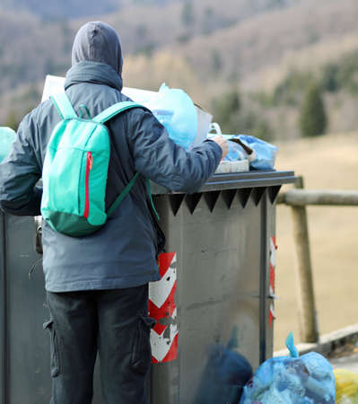 poor boy looks for something to eat in the rubbish bin in winter Stock Photo