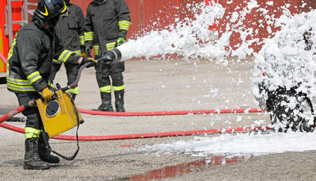firefighter extinguishing with foam the car after road accident