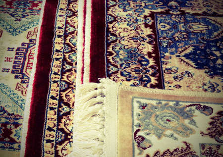 detail of Persian rugs for sale in the ethnic market stall with vintage toned effect