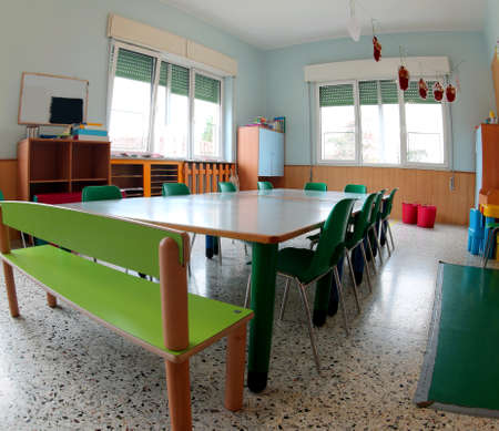 Classroom of a school with green chairs and small table without kids