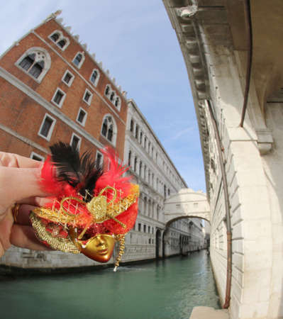 mask and famous Venetian bridge called PONTE DEI SOSPIRI in Venice in Italy with the navigable channel