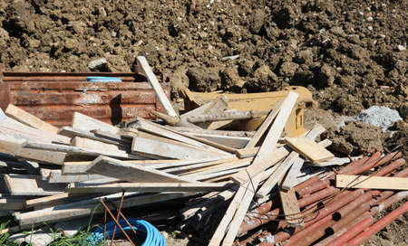 many long wooden boards and more building material on the construction site during the construction of a house