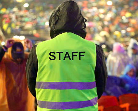 many people during live event and a boy of Staff with yellow high visibility jacket when piss down Stock Photo