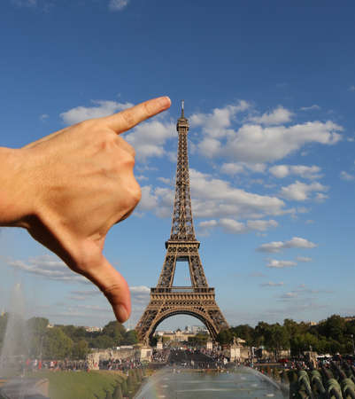 hand of man and measures the Eiffel Tower in Paris France