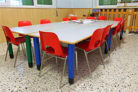 small red chairs and low tables inside a school classroom of the school without the kids Stock Photo