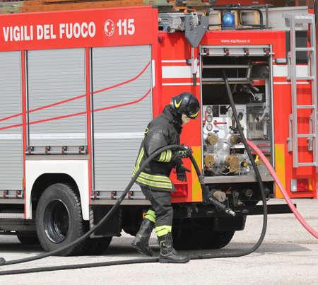 Roma, RM, Italia - 23 maggio 2019: vigile del fuoco con casco e camion dei pompieri con testo VIGILI DEL FUOCO che significa vigili del fuoco in lingua italiana