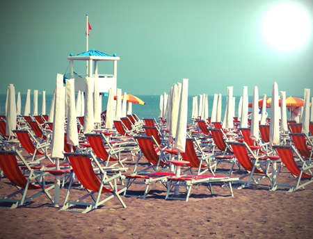 many beach umbrellas and deckchairs  on the resort with old toned effect and a big sun