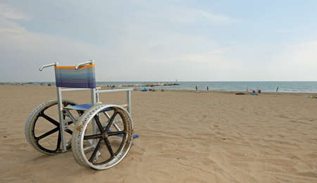 wheelchair on the beach on summer without people Stock Photo