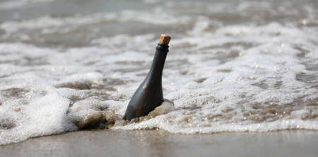 wavees of sea and a bottle of glass with a secret message