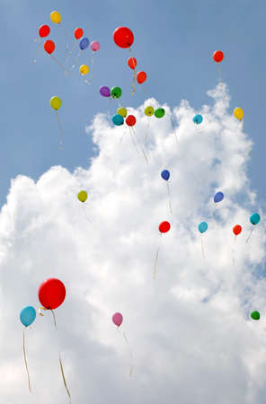 many colorful balloons fly in the sky with white cloud during the celebratory party Фото со стока