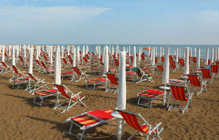 many sun umbrellas and deckchairs  on the sandy beach of the resort in summer