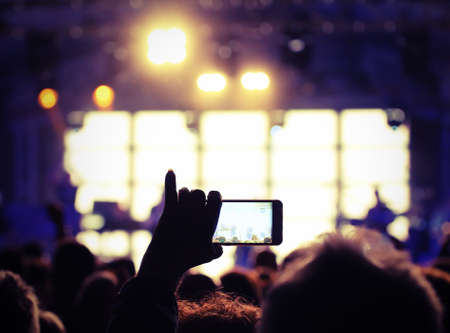 viewer photographs the singer who performs during a concert Imagens
