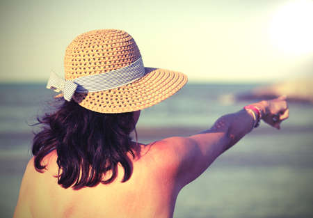 young pretty woman with boater by the sea in summer