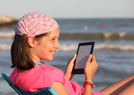 smiling girl reads a digital book facing the sea on the shore 写真素材