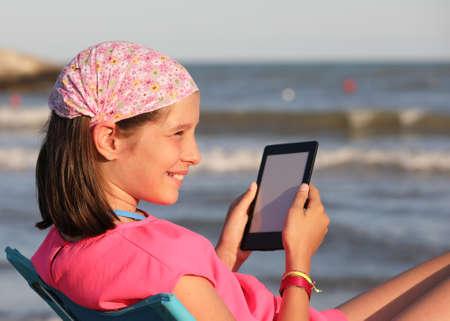 smiling girl reads a digital book facing the sea on the shore Banco de Imagens