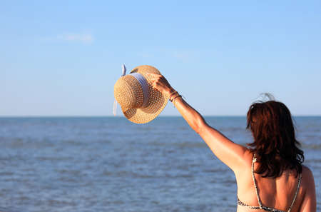 girl greets with straw hat in summer and the ocean in background Imagens