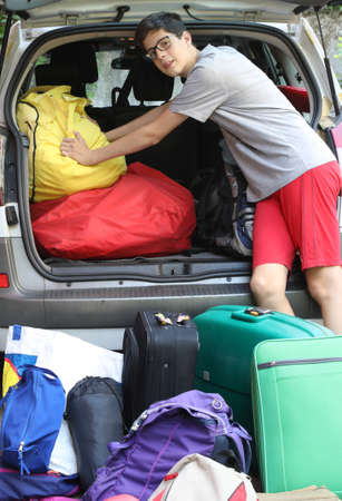 Young boy and his car full of baggages before the travel