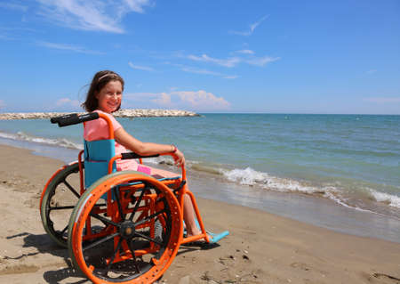 disabled girl sitting in a wheelchair on the shore in front of the sea Stock fotó