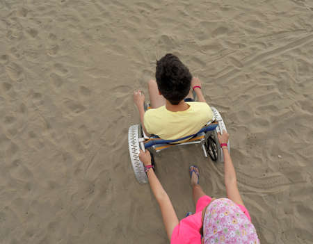 little girl pushes the wheelchair on the sandy beach with a young boy in summer Stock fotó