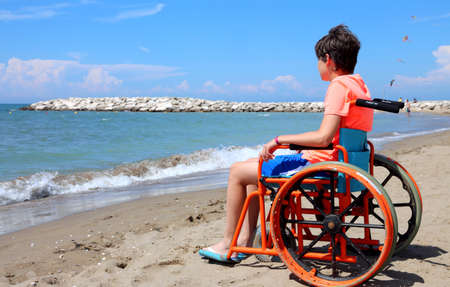 disabled boy sitting in a wheelchair looks at the sea from the shore