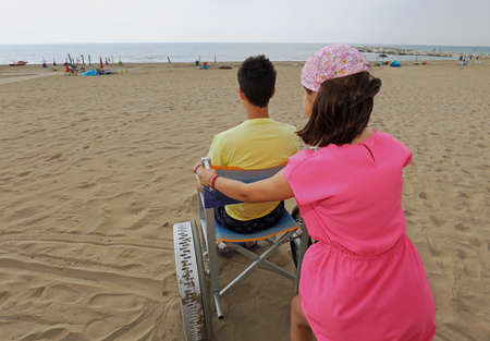 little girl pushes the special wheelchair on the sandy beach with a young boy in summer 写真素材