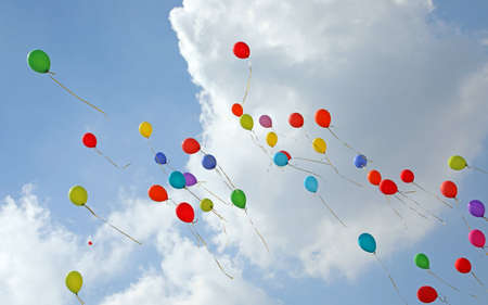dozen of balloons in the blue sky with many clouds symbol of joy and happiness and carefreeness after the party Фото со стока