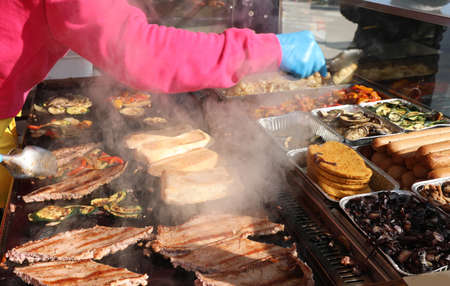 cook with latex gloves while cooking food and sausage on the hot plate of the street food stall