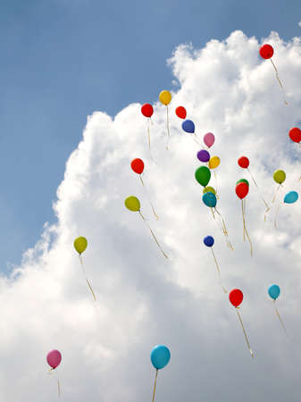 many colored balloons fly up towards the sky
