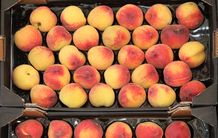 box of organic peaches for sale at market