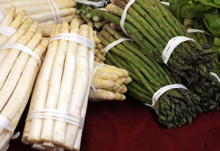bunches of green and white asparagus for sale at the fruit and vegetable market