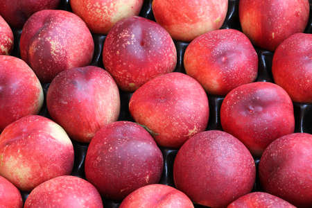 background of organic ripe peaches for sale at market