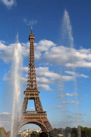 water of Fountain and the Big Eiffel Tower on the blue sky with clouds