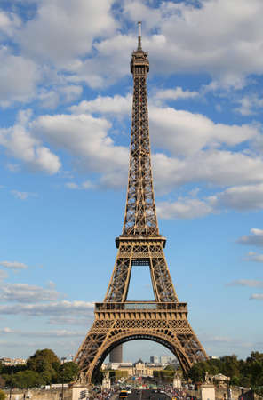High Eiffel Tower Symbol of Paris in France with some white clouds in the blue sky