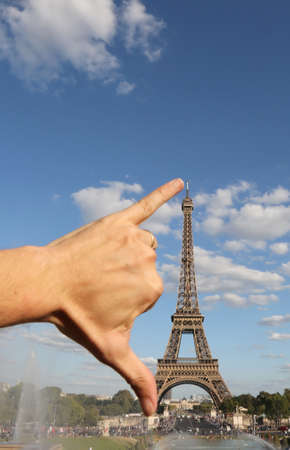 hand that jokingly measures the Eiffel Tower with the span in Paris France Редакционное