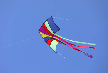 colorful kite flies high in the blue sky