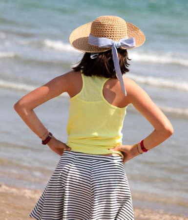 Little girl with straw hat on the beach by the sea in summer