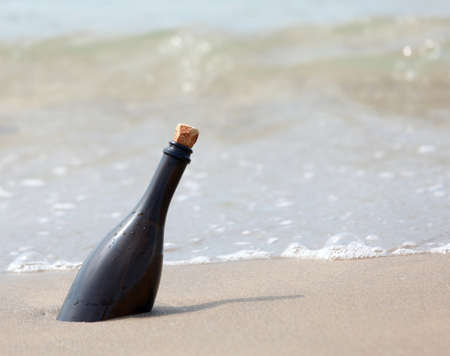 beached glass bottle with secret message on the seashore Imagens