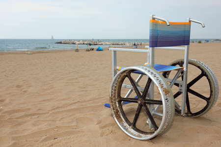 wheelchair without people on the beach in summer
