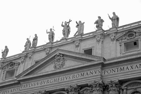 Statues of Saint and Jesus on top of acade of Basilica of Saint Peter in Vatican with black and white effect
