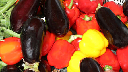 many ripe eggplants and peppers for sale at market