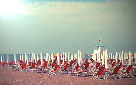 deckchairs and clodes parasoil umbrellas on the beach in summer with old toned effect Imagens