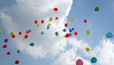 Many colored balloons fly into the blue sky with many white clouds in summer during the party