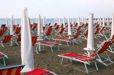 sunshade and deckchairs on the sandy beach without people