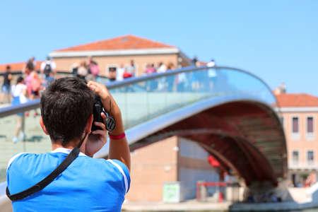 Boy photographs the modern bridge called Ponte della Costituzione that means Constitution Bridge in Venice Imagens