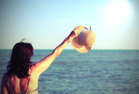 girl greets with boater in summer and the ocean in background with vintage toned effect Imagens