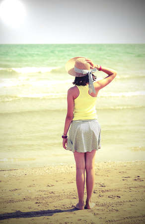 little girl with straw hat also called boater in summer and the sea on background with old toned effect