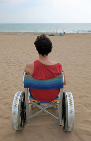 young man on a special wheelchair with big wheels to move on the beach of the resort Imagens
