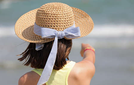 little girl with straw hat in summer and the sea on background