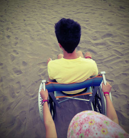 young boy with yellow t-shirt on the wheelchair on the beach with old vintage toned effect